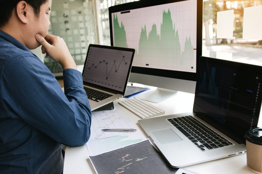 Investors are using laptops entering investment websites stocks market and partners