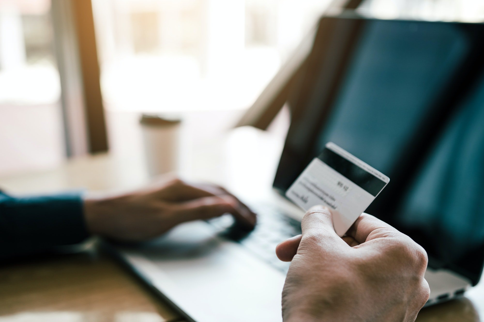 man are holding credit cards and using laptops computers are entering websites