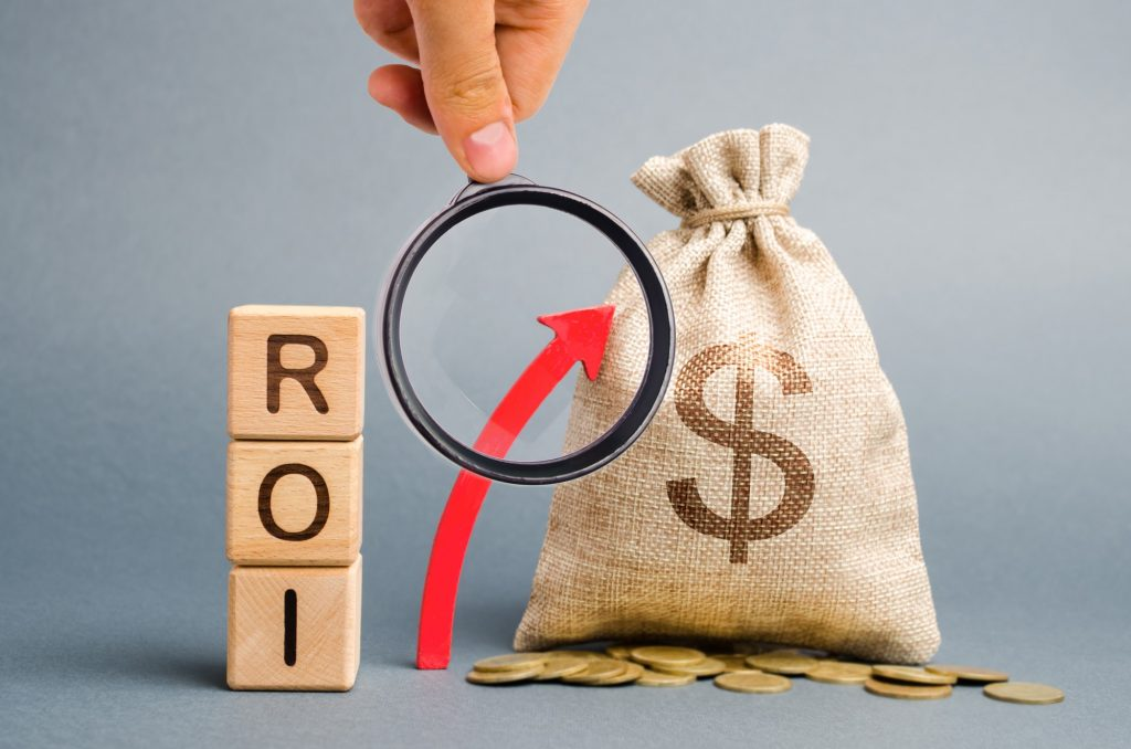Wooden blocks with the word ROI and the up arrow with the money bag